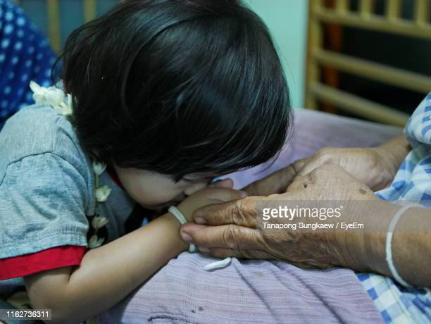 granddaughter kissing hands of grandmother at home - buddhist new year stock pictures, royalty-free photos & images