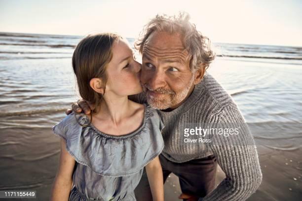 granddaughter kissing her grandfather on the beach - 50 54 jahre stock-fotos und bilder