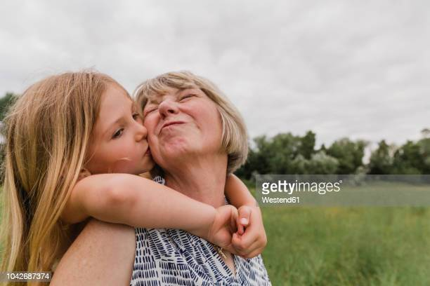 granddaughter kissing her grandmother - grandmother stock pictures, royalty-free photos & images