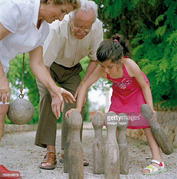 Granddaughter (6-8) playing skittles with grandparents in garden