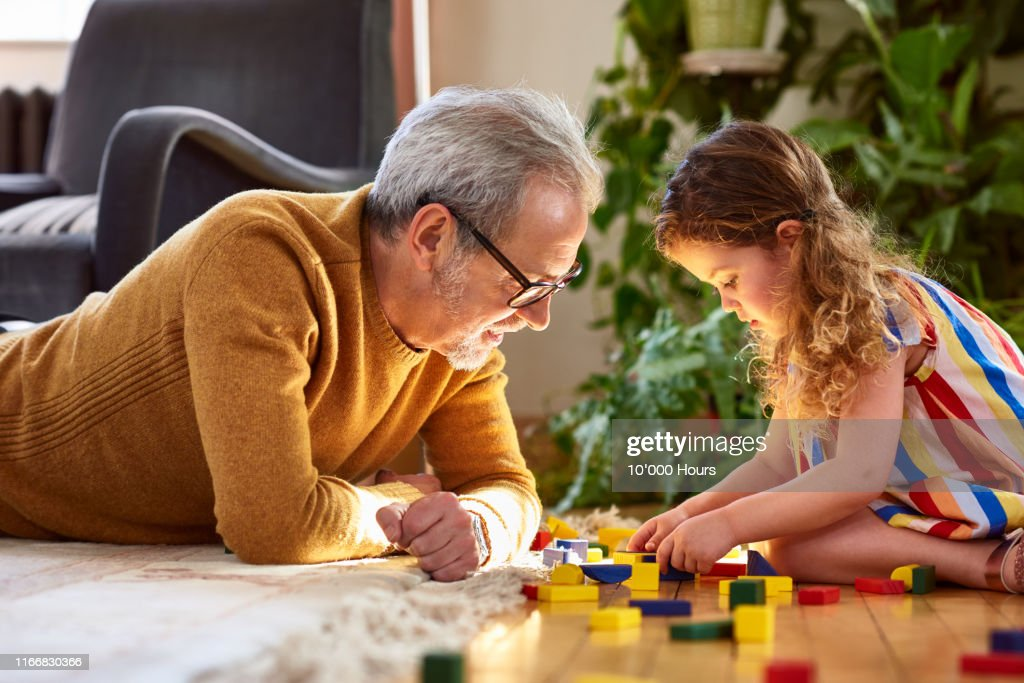 Granddaughter playing with wooden block and granddad watching : Stock-Foto