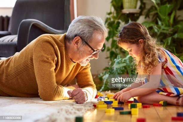 granddaughter playing with wooden block and granddad watching - actieve ouderen stockfoto's en -beelden
