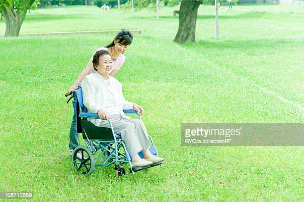 Granddaughter pushing grandmother on wheelchair