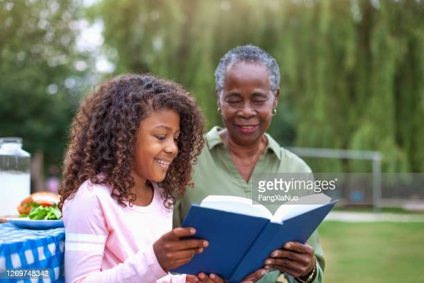 granddaughter reading book with grandmother at public park picnic - history stock pictures, royalty-free photos & images