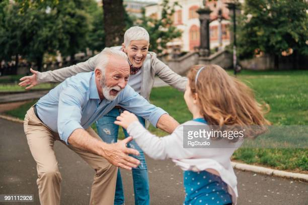 granddaughter running into arms of her grandparents - grandparent stock pictures, royalty-free photos & images