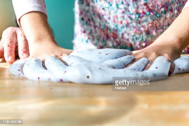 granddaughter spending time together with grandmother making glittering slime in domestic kitchen - slimy stock pictures, royalty-free photos & images