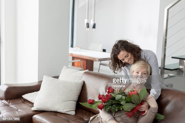 granddaughter surprise grandmother with bouquet of flowers - altruismo foto e immagini stock