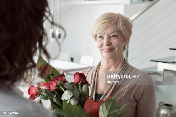 Granddaughter surprise grandmother with bouquet of flowers