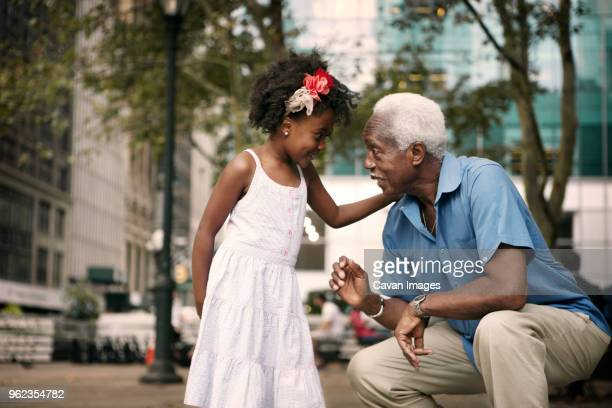 Granddaughter talking to grandfather while sitting in city