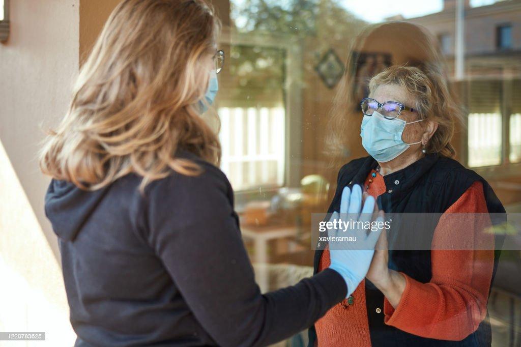 Granddaughter visiting grandmother during pandemic : Stock Photo
