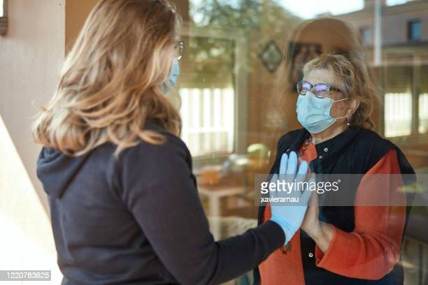 granddaughter visiting grandmother during pandemic - senior adult stock pictures, royalty-free photos & images
