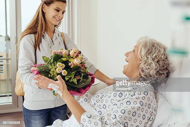 Granddaughter visiting grandmother in hospital, bringing bunch of flowers