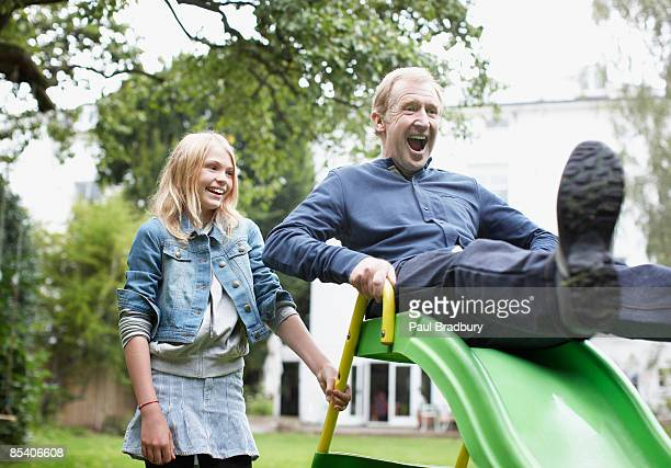 granddaughter watching grandfather sliding on play equipment - young at heart stock pictures, royalty-free photos & images