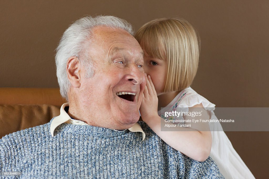 Granddaughter whispering to Grandfather : Stock Photo