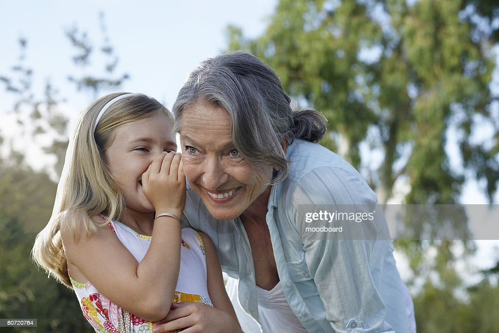 Granddaughter (5-6) whispering to grandmother's ear outdoors : Stock Photo