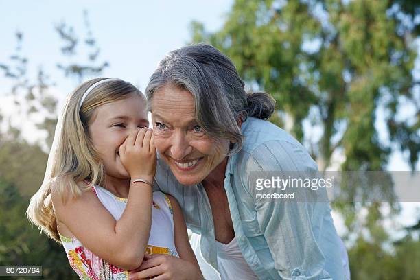 Granddaughter (5-6) whispering to grandmother's ear outdoors