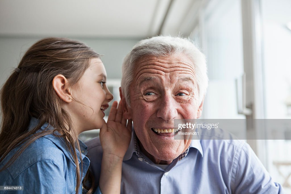 Granddaughter wispering something in the ear of her grandfather : Stock Photo