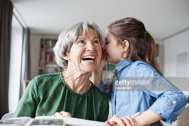 Granddaughter wispering something in the ear of her grandmother
