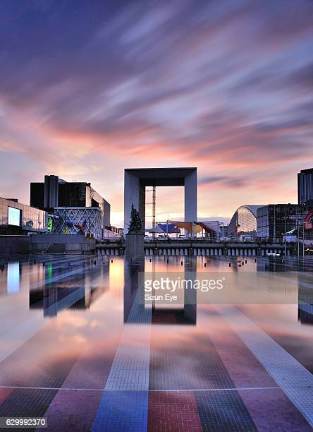 Grande Arche of La Défense, the business district of Paris reflected in fountain, at twilight, France.