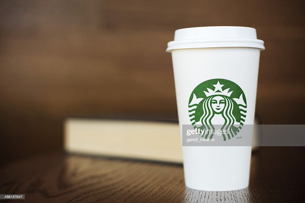 Grande Starbucks to go cup on wooden table with book : Stock Photo