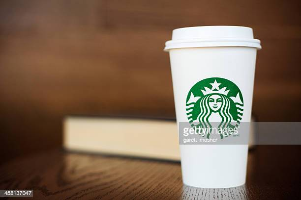 Grande Starbucks to go cup on wooden table with book