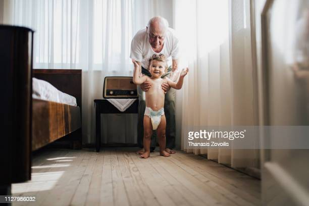 Grandfarher helping his grandson to walk