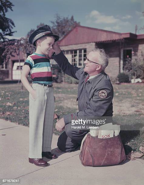 grandfather adjusting cap of his grandson  - uniform cap stock pictures, royalty-free photos & images