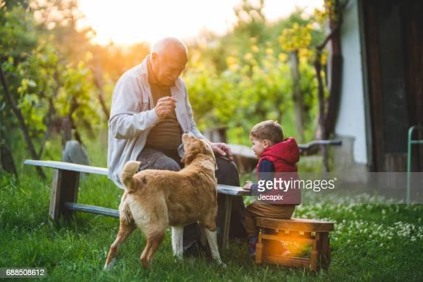 Großvater und junge spielt mit Hund