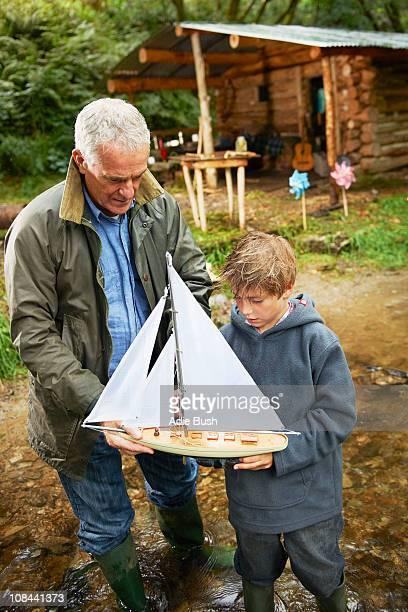 Großvater und junge mit Segelboot