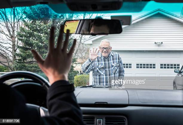 grandfather and car driver grandson waving goodbye through windshield - waving gesture stock photos and pictures