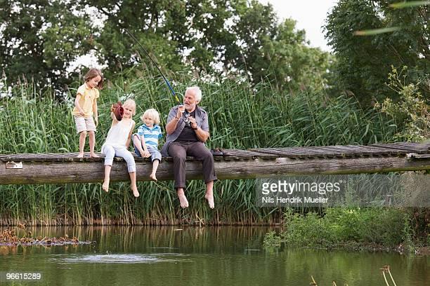 grandfather and children fishing - angeln stock-fotos und bilder
