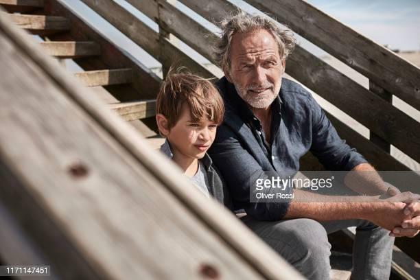 grandfather and gandson sitting on footbridge at the beach - 50 54 jahre stock-fotos und bilder
