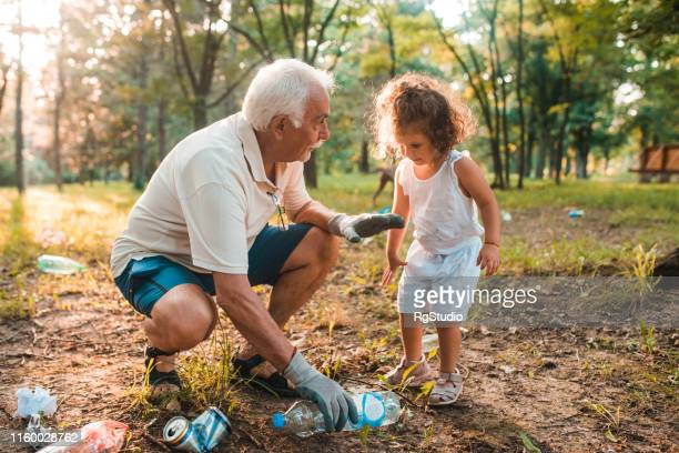 grandfather and girl recycling - selfless stock pictures, royalty-free photos & images