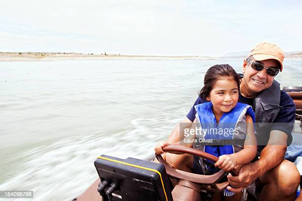 grandfather and grandaughter driving boat - life jacket stock pictures, royalty-free photos & images