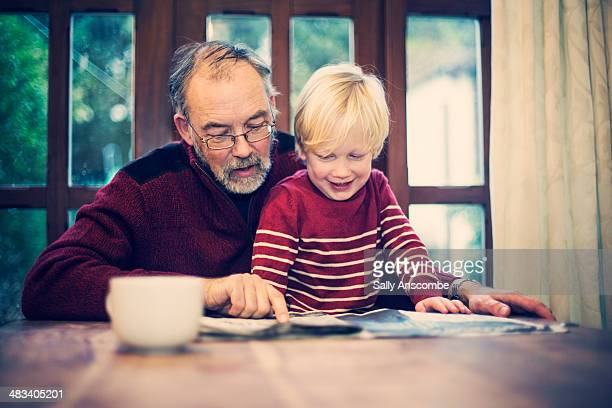 Grandfather and Grandchild reading the paper