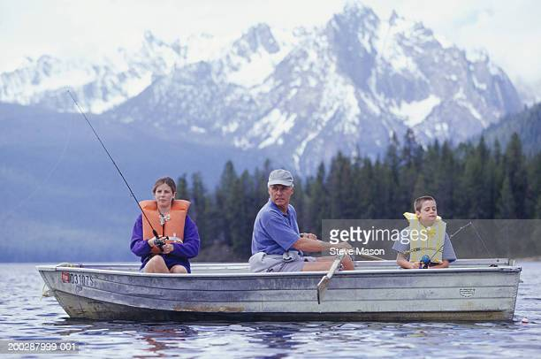 Grandfather and grandchildren (10-11) (14-15) fishing in boat on mountain lake