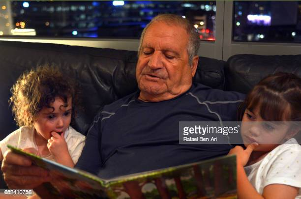 grandfather and grandchildren reading a book - rafael ben ari stock pictures, royalty-free photos & images