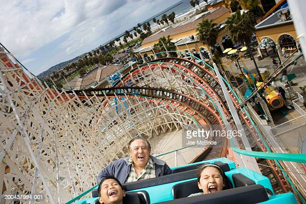 Grandfather and grandchildren (9-11) riding rollercoaster