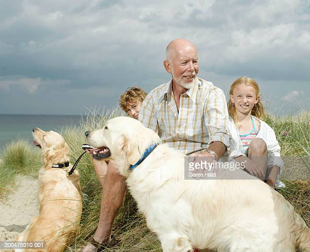Grandfather and grandchildren (7-11) sitting with dogs on beach