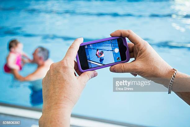 Grandfather and granddaughter (12-23 months) being photographed in swimming pool