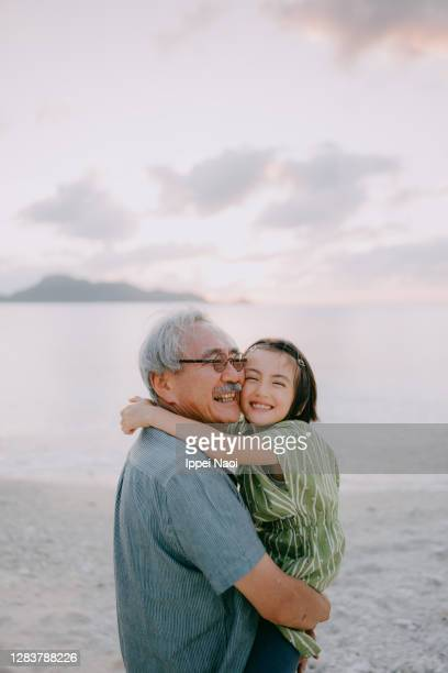 grandfather and granddaughter cuddling on beach at sunset - tropical climate stock pictures, royalty-free photos & images