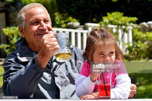 grandfather and granddaughter drinking  cold drinks - rafael ben ari stock pictures, royalty-free photos & images