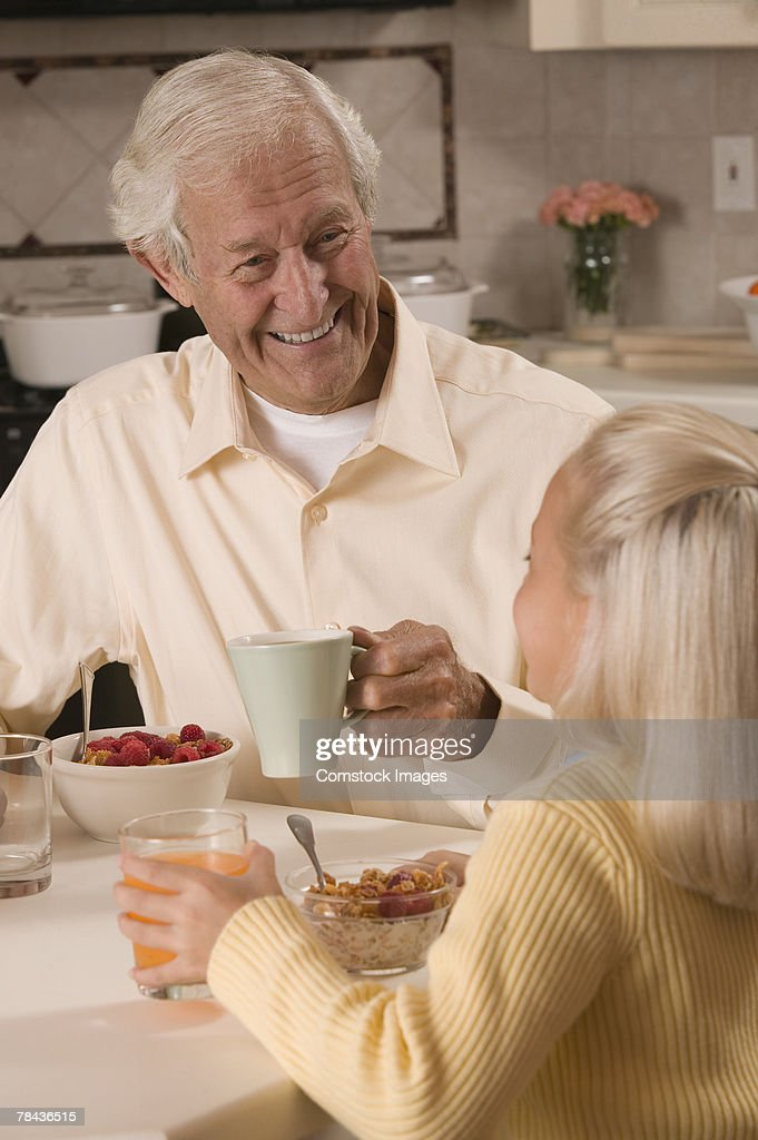 Grandfather and granddaughter eating breakfast : Stockfoto