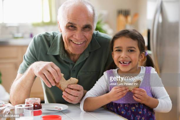 grandfather and granddaughter eating sandwiches - peanut butter and jelly sandwich stock pictures, royalty-free photos & images
