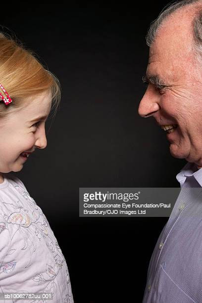 Grandfather and granddaughter (8-9) face to face, smiling, profile