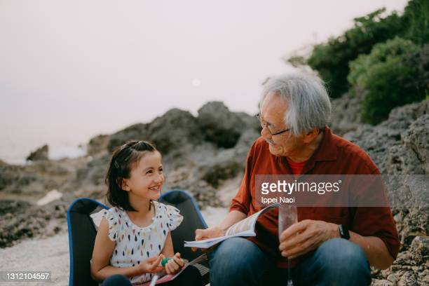 grandfather and granddaughter having a good time at beach campsite - grandfather stock pictures, royalty-free photos & images