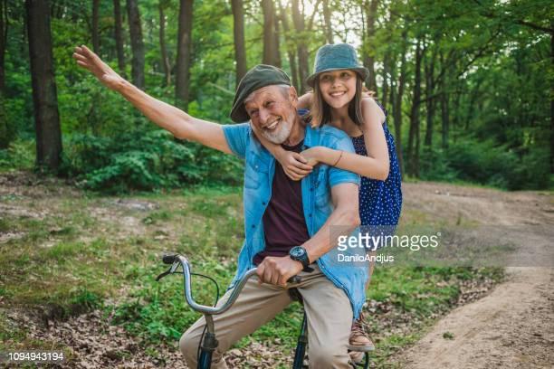 grand-père et sa petite-fille s'amuser ensemble - velo humour photos et images de collection