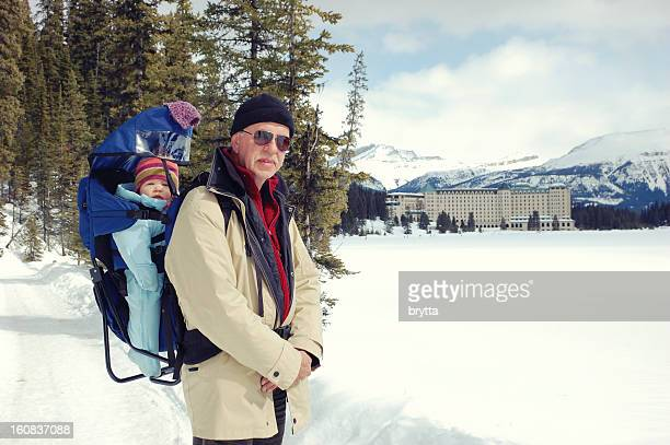 grandfather and granddaughter hiking on a frozen lake louise, canada - chateau lake louise stock photos and pictures