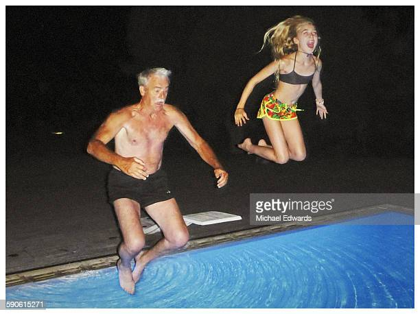 grandfather and granddaughter jumping tinto pool