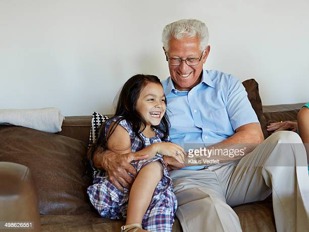 Grandfather and granddaughter laughing in sofa